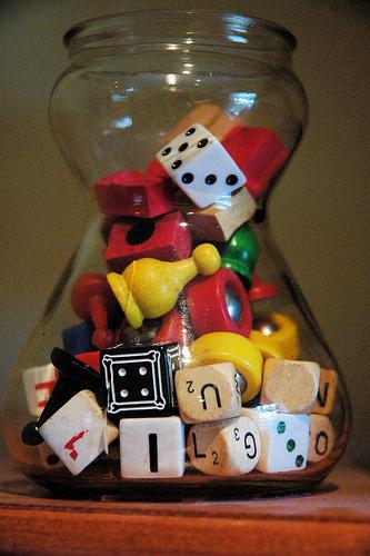 Um pote com diversas pecinhas de jogos de tabuleiro