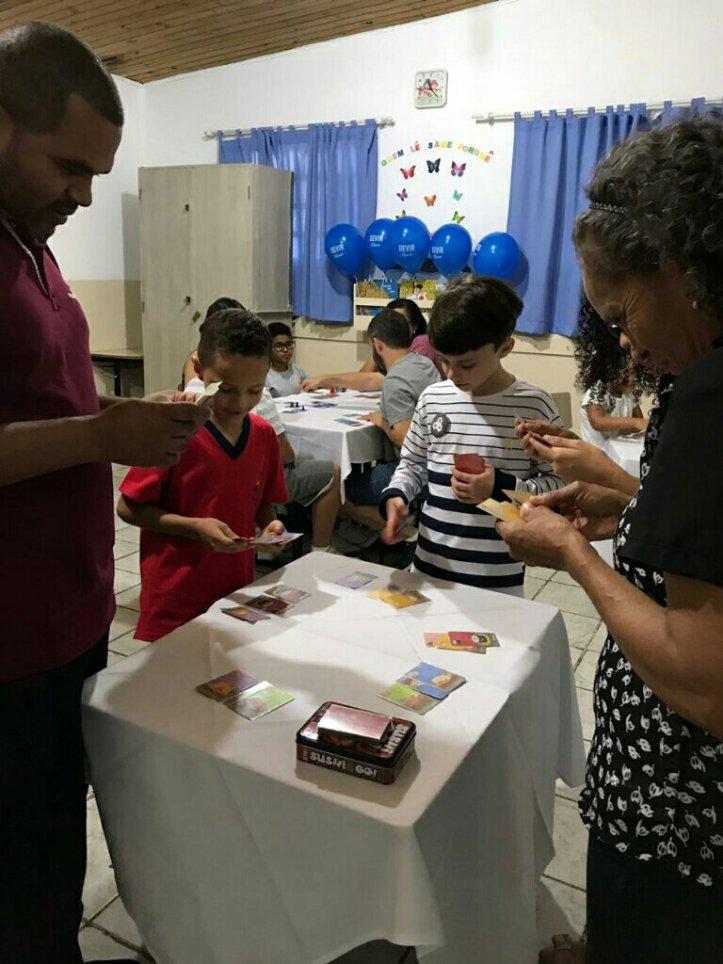 Criançada jogando Sushi Go! na festa da Família na escola Cristã Jardim das Oliveiras
